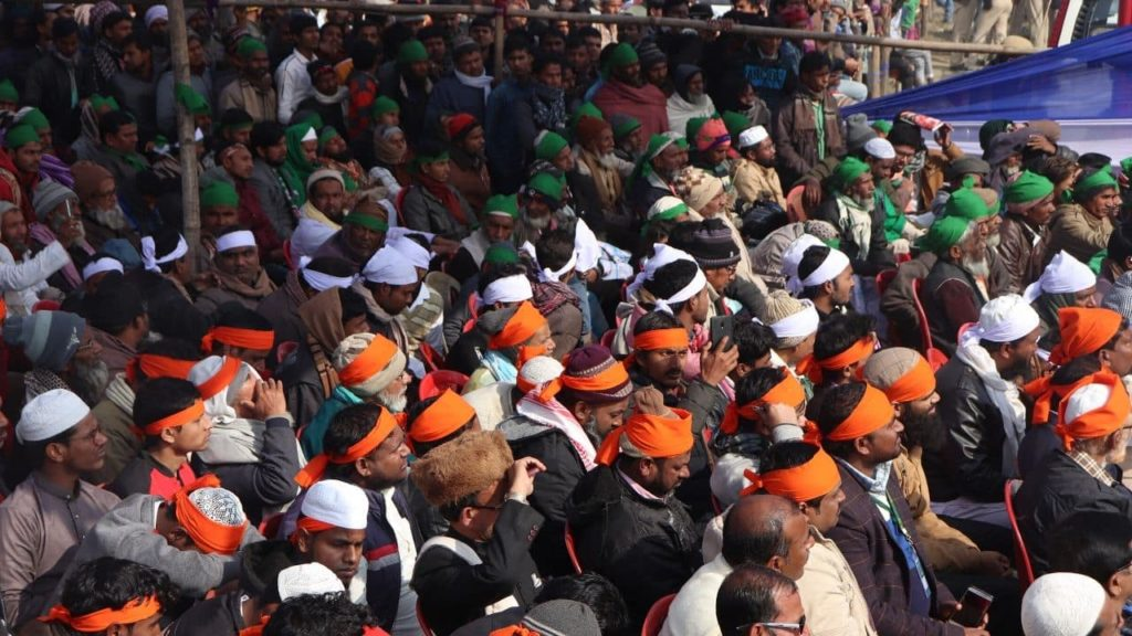People wearing headgear sitting in a tricolor formation in Owaisi's rally ij Kishanganj
